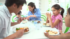 Asian Family Sitting At Table Eating Meal Together Stock Footage