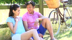 Asian Couple Resting By Fence With Old Fashioned Cycle Stock Footage