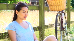 Asian Woman Resting By Fence With Old Fashioned Cycle Stock Footage