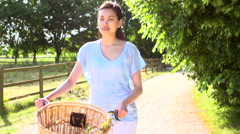 Asian Woman Pushing Old Fashioned Cycle Along Country Track Stock Footage