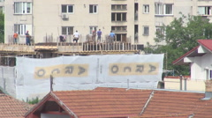 Construction workers on rooftop working hard, building new house in residential Stock Footage