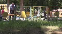 Playground view, grandfather with nephews playing outside in park, rocking chair Stock Footage