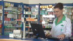 Beautiful pharmacist working inside pharmacy at desktop computer, pills on shelf - stock footage