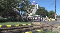 Old tram in station, crowd of people crossing zebra mark on street, rail view Stock Footage