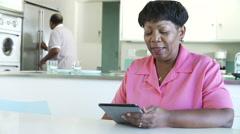 Senior Woman Using Digital Tablet As Husband Makes Breakfast Stock Footage