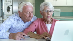 Senior Couple Booking Vacation Online Using Digital Tablet - stock footage