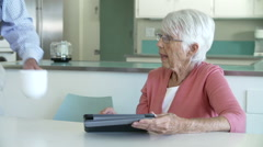 Senior Couple Sitting At Kitchen Table Using Digital Tablet Stock Footage