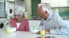 Senior Couple Having Breakfast In Kitchen Together Stock Footage