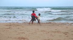 The view of a three local kids playing on a beach in Matara. Stock Footage