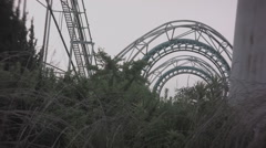Overgrown roller coaster at abandoned theme park. 0551 Stock Footage