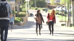 Female Students Walking Outdoors On University Campus Stock Footage