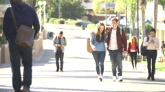 Student Couple Walking Outdoors On University Campus Stock Footage