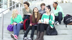 Group Of High School Students Sitting Outside Building Stock Footage