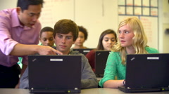Teacher Helping High School Students Using Laptops In Class - stock footage