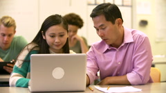 Female High School Student With Teacher Using Laptop - stock footage