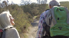 Senior Couple Hiking Along Country Path Together Stock Footage