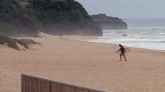 Surfer Walking across the Beach Stock Footage