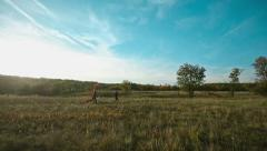 Happy Couple Runing Across the Field at Sunset Stock Footage
