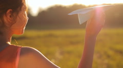 Young girl looks at the sun and throws a paper airplane, childhood, sunset Stock Footage
