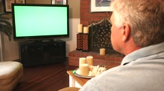 Man Watching Greenscreen on a Big Screen TV 4K Stock Footage