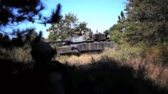 U.S. Marines conduct Tank Maneuvers - Tank drives over ridge in the forest - stock footage