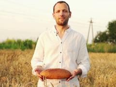 Farmer holding fresh bread in wheat field, super slow motion, 240fps NTSC Stock Footage