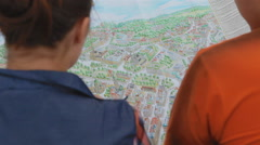 Boy and girl are considering a city map and discuss Stock Footage