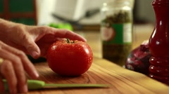 A chef cuts a juicy red tomato Stock Footage