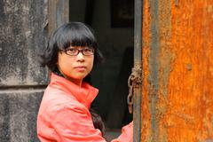 Portrait of a young woman and rusty old door - stock photo