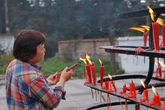 Old woman burning joss sticks on the summit of Emei mountain - stock photo