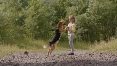 Little girl plays with a dog on a chain Stock Footage