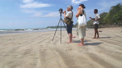 Japanese tourist photographing local people on the beach in Weligama. Stock Footage