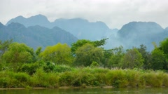 Bank of the river and high mountains in the background. laos, vang vieng Stock Footage