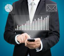 businessman standing posture hand hold mobile phone analyze graph isolated - stock photo