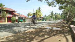 Man on a bicycle nearly getting knocked over on street of Weligama. Stock Footage