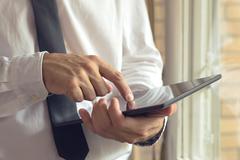 Businessman taps digital tablet computer Stock Photos