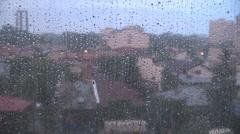 Rain drops on window, thunder lighting the village, above houses on rainy day  Stock Footage