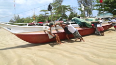 Fishermen pushing boat on sand into the ocean in Weligama. Stock Footage