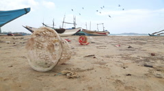 Trash washed up on shore in front of wooden fishing boast on beach. Stock Footage