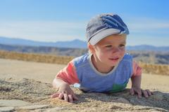 Little boy laying down on the rock - stock photo