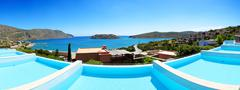 panorama of swimming pools at luxury hotel with a view on spinalonga island, - stock photo