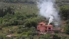 Villa in countryside with white smoke Stock Footage