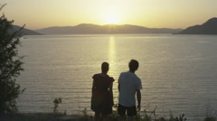 Happy couple dancing softly to the sun set. 4K slow motion.  Stock Footage