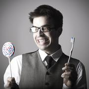 Happy smart young man with a lollipop in one hand and a toothbrush in the oth Stock Photos