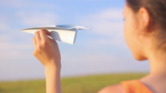 Young girl holding a paper plane, dream, close-up, travel, future Stock Footage