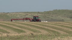 Case Tractor Raking Over Hill Far Shot - stock footage
