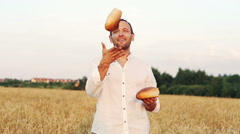 Young, happy farmer juggle bread among field super slow motion, 240Fps HD Stock Footage
