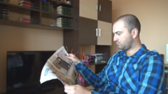Business man in the living room reading newspaper, relaxing, focused on the news Stock Footage