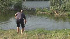 Young man fishing on lake, catching lake weed smiling enjoying his water hobby  Stock Footage