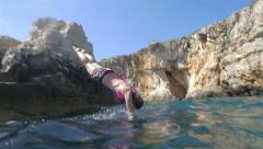 SLOW MOTION: Woman jumps into the ocean - stock footage